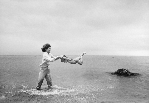 Jackie swings Caroline in the shallows at Hyannis Port 1959